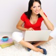 Beautiful young woman sitting with notebook in room — Stock Photo #26029885