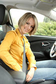 Portrait of young beautiful woman attaching seat belt in the car — Stock Photo