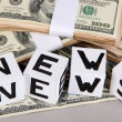"White paper cubes labeled ""News"" with money on grey background — Stock Photo"
