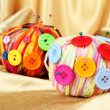 Colorful buttons and multicolor wool balls, on color fabric background — Stock Photo #26064631