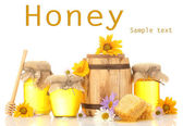Honey in banks and barrel isolated on white — Stock Photo