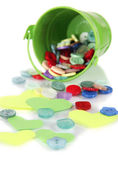 Colorful buttons strewn from bucket isolated on white — Stock Photo