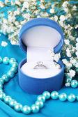 Kwiaty i pierścionek zaręczynowy na niebieski tkaniny — Zdjęcie stockowe
