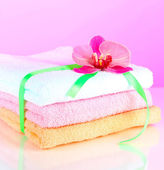 Towels tied with ribbon on light pink background — Stock Photo