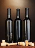 Wijn en kurken op houten tafel op bruine achtergrond — Stockfoto