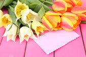 Beautiful white and orange tulips on color wooden background — Stock Photo
