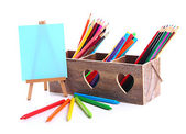 Different pencils in wooden crate and easel, isolated on white — Stock Photo