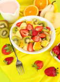 Useful fruit salad of fresh fruits and berries in bowl on tablecloth close-up — Stok fotoğraf