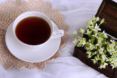 Composition with spring flowers and cup of tea on white satin background — Stock Photo