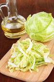 Verde cavolo, olio, spezie sul tagliere, su fondo in legno — Foto Stock