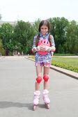 Little girl in roller skates at park — Stock Photo