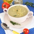 Nourishing soup in pink pon blue tablecloth close-up — Stock Photo #26150879