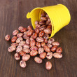 Overturned bucket with beans on wooden background — Stock Photo