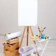Wooden easel with clean paper and art supplies in room — Stock Photo