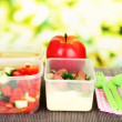 Tasty lunch in plastic containers, on bamboo mat on bright background — Stock Photo