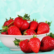 Strawberries in plate on blue background — Stock Photo #26152287