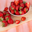 Strawberries in bowl on cutting board on wooden table — Stock Photo #26152385
