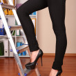 Woman climbing up ladder in office — Stock Photo #26153293