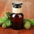 Bottle of fir tree oil and green cones on wooden background — Стоковая фотография