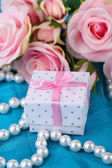 Rose and gift on blue cloth — Stock Photo