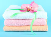 Towels tied with ribbon on blue background — Stock Photo