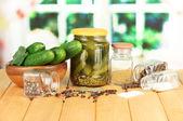 Gustosi cetrioli freschi e in scatola, sul tavolo di legno su sfondo luminoso — Foto Stock