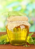 Tarro de miel con las flores de la cal, en mesa de madera sobre fondo brillante — Foto de Stock