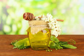 Jar of honey with flowers of lime, acacia on wooden table on bright background — Stock Photo