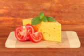 Cheese,basil and tomato on cutting board on wooden background — Stock Photo