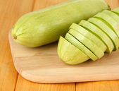 Fresh marrows on cutting board, on wooden background — Stock Photo