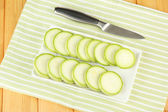 Fresh marrows on plate, on wooden background — Stock Photo