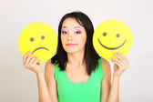 Giovane donna con carta con smiley triste e felice su sfondo grigio — Foto Stock