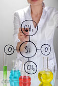 Chemist woman writing formulas on glass on grey background — Stock Photo