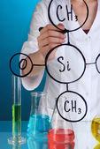 Chemist woman writing formulas on glass on blue background — Stock Photo