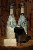 Composition with old bottle of wine and wineglass in old cellar, on dark background — Stock Photo