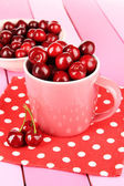 Cherry berries in cup and bowl on wooden table close-up — Stock Photo