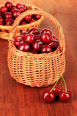 Cherry berries in wicker baskets on wooden table close-up — Stock Photo