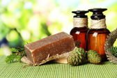 Hand-made soap and bottles of fir tree oil on bamboo mat — Stock Photo