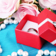 Rose and engagement ring on blue cloth — Stock Photo #26194613