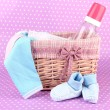 Beautiful basket of baby clothes on a pink background — Stock Photo