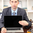 Young businessman with laptop computer facing on his workplace — Stockfoto