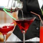 Barmen hand met gieten cocktail shaker in glas, op lichte achtergrond — Stockfoto