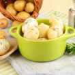 Tender young potatoes with sour cream and herbs in pan on wooden board on table close-up - Stock Photo