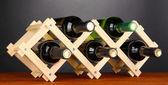 Bottiglie di vino inserito su supporto in legno su sfondo grigio — Foto Stock