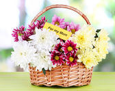 Bouquet of beautiful chrysanthemums in wicker basket on table on bright background — Stockfoto