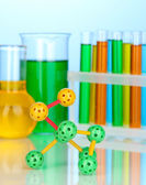 Molecule model and test tubes with colorful liquids on blue background — Photo