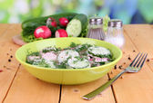 Vitamin vegetable salad in bowl on wooden table on natural background — Stock Photo