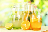Orange and lemon lemonade in pitchers and glasses on wooden table on natural background — Stock Photo