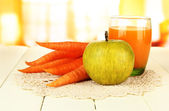 Heap of carrots and green apple, glass of juice, on color wooden table on bright background — Stock Photo