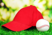 Red peaked cap on grass on natural background — Stock Photo